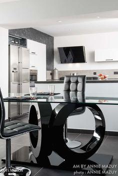 Ce meubles noir brillant aux courbes géométrique est la pièce maitresse de cette salle à manger.