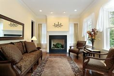 Small enclosed living room at the front of the home with black fireplace, wood floors and brown furniture.