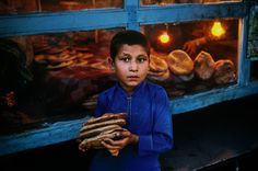 Steve McCurry — Our Daily Bread All sorrows are less with bread....