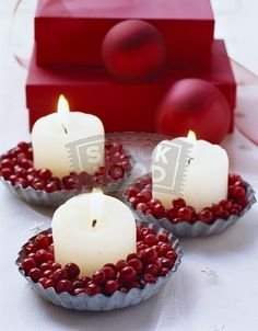 Tiny fluted tin filled with cranberries with small white votive