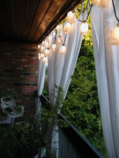 For extra balcony privacy, try hanging a simple curtain, and illuminating it with a pretty string of lights. (via Apartment Therapy) #balconygarden