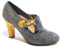 1920's / 1930's style high heel T-strap with patent leather trim, grosgrain piping, and contrast perforations. Leather, suede and/or patent uppers with leather