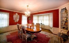 Dining room in colonial home with red silk wallpaper and white crown moulding and wainscoting. Also includes built-in display shelves, a chandelier and oak hardwood floors.