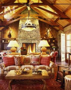 A California Family Ranch House - the great room with back-to-back sofas upholstered in a favorite Brunschwig printed linen, all sitting on a huge custom red rug. When AD published this, they edited out the animal heads from the photos.