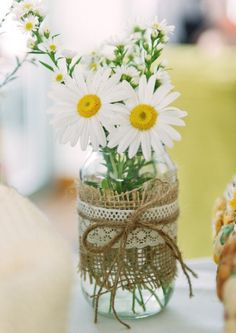 Daisies in a jar wrapped in burlap for centerpieces