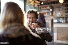 Stock Photo : Man having coffee while looking at woman in cafe