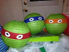 Diy Ninja turtles birthday party decoration. Wrap streamer around green paper lantern (partycity). Cut out white paper in the shape of eyes, color in eyeballs with black sharpie! Last hang from ceiling, easy and very cute!