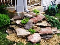 Gather up a collection of large, lagged stones and place them stacked underneath or in front of one of the eaves trough drains around your house. It'll filter the water coming down and help guide it away from your house with style.