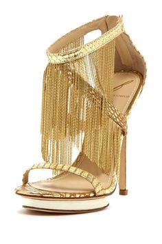 Designer:  Brian Atwood There is more than just the colour gold that is a reminder of the chair. The fringes on the shoe forming a rectangular shape is also a reminder of fringes on the chair and its shape. Also, the gold border at the ankle and toes also look like the ribbon surrounding the fabric of the chair. Finally, this chair is great in height compared to the average chair which is reminded by the fact that this shoe is a heel and therefore, allows more height than a regular shoe as…