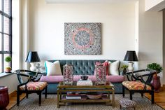 An eclectic yet timeless living space with abstract art, tufted blue sofa, and colorful pillows