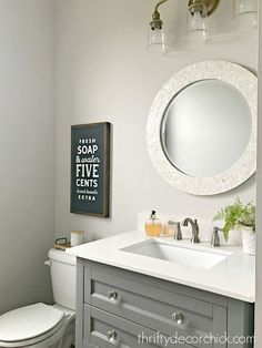 I love the overall look of this calm powder room. Capiz round mirror and love the word-art over the toilet.