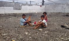 Child scavengers burn a toxic plastic cover off a wire to salvage the copper inside, in San Juan City, Manila. Photograph: Donald Brown
