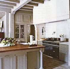 Warm kitchen. Butcher block countertop.  Break up the white with another neutral.