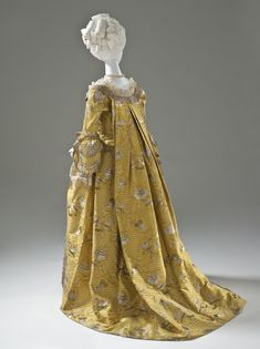 Back view, robe à la Francaise, England, c. 1760. Yellow silk plain weave with weft-float patterning and silk with metallic-thread supplementary-weft patterning, and metallic lace.