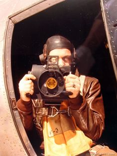 U.S. Army Air Force S/Sgt. hold his Graflex K-20 aerial camera at waist window of B-17 Flying Fortress in England.