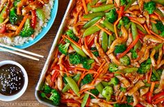 A sheet pan with chicken teriyaki and vegetables next to a plate with rice and chopsticks