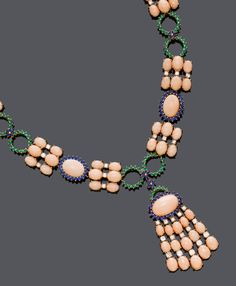 CORAL, SAPPHIRE, EMERALD AND DIAMOND NECKLACE. Pink gold 585, 92 g. A sequence of 5 pale-pink corals within a sapphire surround, 5 emerald-set ring motifs, and 10 links set with 6 corals and 3 brilliant-cut diamonds. The pendant set with 1 pale-pink coral within a sapphire surround, and 5 lines of corals and brilliant-cut diamonds. Total coral weight ca. 124.00 ct, total sapphire and emerald weight ca. 16.00 ct, and total diamond weight ca. 4.00 ct. L ca. 45 cm.