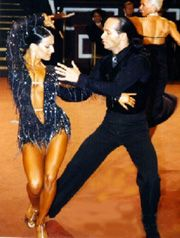 """The Rumba originates from Cuba as a typical dance of a hot climate. It has become the classic of all the Latin American dances. In its present form many of the basic figures of the dance retain the age-old story of woman's attempt to dominate man by the use of her feminine charm. In a well choregrphed dance there will always be an element of """"tease and run""""; the man being lured and then rejected."""