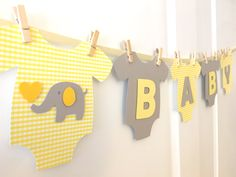 **Cute and adorable banner for baby showers!!** This banner is a perfect touch for both gender neutral baby showers! Light Yellow plaid patterned and sold Gray one-piece bodysuits are made of high quality heavy cardstock paper and strung on ivory satin ribbon using mini wooden clothespins. Alternating light yellow and gray WELCOME BABY letters and the center elephant design are mounted with pop-dots, adding that special something with a 3D look! - Each bodysuit measures about 6.5 in width…