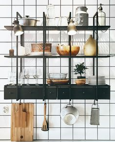 Two dark metal open shelving units with plates, glasses and kitchen stuff on a white tile wall.