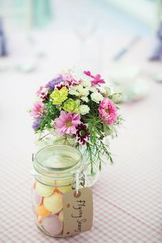 instead of sweets table, mini mason jars filled with pastel coloured sweets as part of table decor.