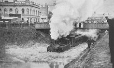 Flooded railway tracks with train passing under the bridge that crosses Chapel Street, near Arthur and Palermo Street. 25 January 1907.Melbourne Victoria Australia