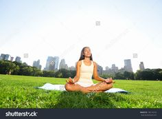 Meditating woman in meditation in New York City Central Park in yoga pose. Girl relaxing with serene relaxed expression outside in summer. Beautiful young mixed race Asian Caucasian female model.