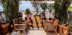O pergolado, em um canto do terraço, possui paisagismo de Claudia Muñoz. O piso tem área central forrada de pedriscos e entorno de deque de pínus tratado, executado pela construtora do prédio (Foto: Victor Affaro)