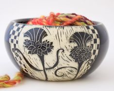 Two etched thistles are featured on this yarn bowl by Patricia Griffin in Cambria, Ca. It's handmade and has slot in back for yarn. Check them out online at patriciagriffinceramics.com