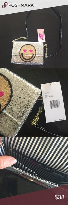 Betsey Johnson clutch Betsey Johnson silver shimmer clutch, smiley gold face on front, silver with logo on back.  Removable crossbody strap with gold chain detail.  Magnetic snap closure.  Two open pockets and a zip pocket inside.  NWT Betsey Johnson Bags