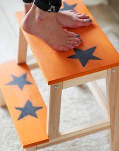 Close up of customized BEKVAM step stool painted orange with black stars.