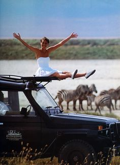 """Bianca is like a little child!  She just can't get enough of this lovely view around here.  She climbs onto one of the jeeps and poses so that Jackie can get a photo of her """"surfing the Serengeti"""" for Bianca's journal.  This picture will end up to be one of her very favorites of the trip!"""