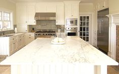 White & gray kitchen design with gray glass tiles backsplash, white beadboard kitchen island, white kitchen cabinets, marble countertops, sink in kitchen island, brick fireplace in kitchen and pot filler.