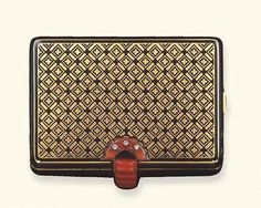 AN ART DECO CORAL, ENAMEL AND GOLD VANITY CASE, BY CARTIER The rectangular-shaped polished gold case, decorated on the lid and reverse with black enameled Chinese 'earth pattern', to the black enameled spotted sides, with a carved coral sliding clasp, accented by diamond collets and black enamel detail, opening to reveal a fitted mirror, covered compartment, and lipstick holder, mounted in 18k gold, circa 1925 (Christie's)