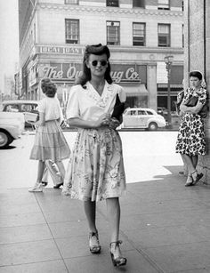 Vintage 40s skirts on the ladies...I am wondering if that's an old Owl Drugstore in the back.