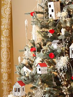 Decorate a Christmas tree with repeated simple elements. Incorporate the crystallized theme with glass icicles and snowflakes, tiny white lights, and dots of red. Add the little house ornaments and strands of clear glass beads