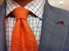 An orange tie looks great with this grey/blue jacket