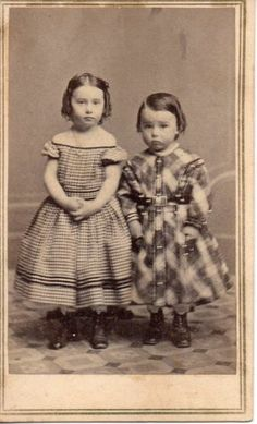 Brother and sister, you can tell young boys from young girls, not from their clothes (they are rather similar) but from their hair. Notice the side part on the boy and center part on the girl