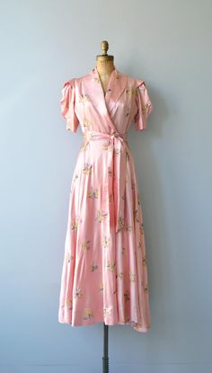 Vintage 1940s pink satin and small floral embroidered wrap dress/dressing gown with puff short sleeves, wide open lapel  neckline, long self-fabric sash belt and dramatic sweep. Also has closure at the waist. ✂-----Measurements  fits like: extra small bust: 34-38 waist: 25 length: 57 brand/maker: n/a condition: excellent  to ensure a good fit, please read the sizing guide: http://www.etsy.com/shop/DearGolden/policy  ✩ visit the shop ✩ http://...