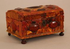 German amber jeweller's casket, in rectangular form with rounded lid. The wooden casket decorated all over with yellow, orange and red amber plates in geometrical shape. Metal hinges, lock, four screws and lock mount. On four different bun feet.