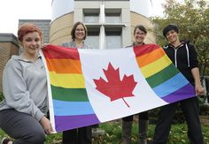 From left: Monsignor Doyle student Leaah Robson, 15, Chaplain Marianna Worth, teacher Annie Denomme and student Melissa Lee, 18, display a Canadian flag with rainbow colours in front of the high school on Friday.