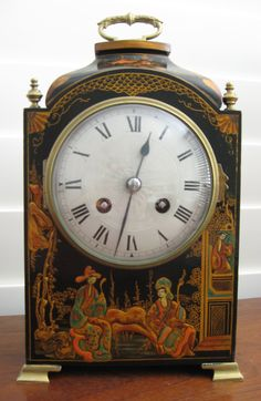 Decorative black Chinoiserie bracket clock with silvered engine turned face.  Chimes hours on a gong.