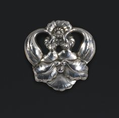 A Georg Jensen silver flower brooch, Copenhagen, 1933-1944 in the form of an orchid, in a case with inscription 'Frederic Robinson / Camberley / Hand Wrought Silver / by / Georg Jensen.' 4.2cm., 1 5/8 in wide