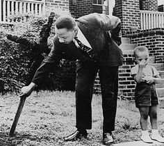 Martin Luther King Jr removing a burned cross from his front yard with his son at his side. Atlanta Ga 1960