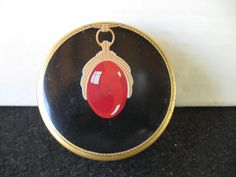 This is a vintage Ruby Pendant typewriter tin. It is black with gold accents and a red ruby pendant in the middle of the tin. Tin is in great shape