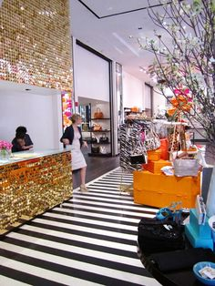 Gold sequin wall with black & white stripe floor at Kate Spade nyc