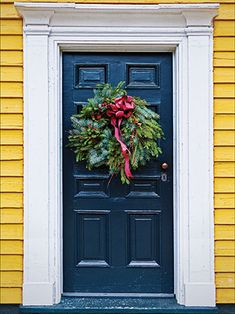 A house with bright yellow siding, dark blue door, and Christmas wreath are the centerpiece of our Cambridge Door backdrop.