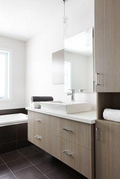 Mélamine texturée tons de crème et comptoirs en stratifié sont les acteurs principaux de cette salle de bains au style moderne. Le mur est habillé d'un miroir sans cadre, apposé sur un panneau plat, fabriqué avec le même matériel que les armoires.