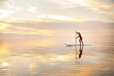 Caroline Gleich paddle boarding at sunset