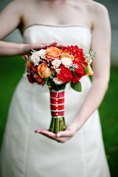 Orange, red, and white bridal bouquet wrapped and pinned in red ribbon. Photo: EyeSpy Photography